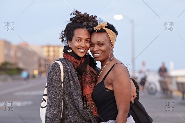African American friends hugging on sidewalk