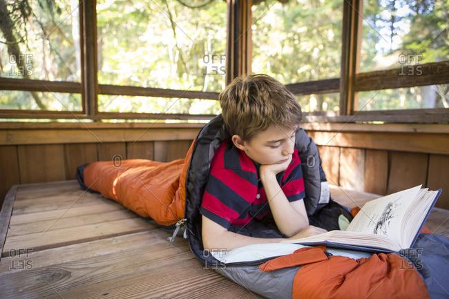 Caucasian boy reading in sleeping bag