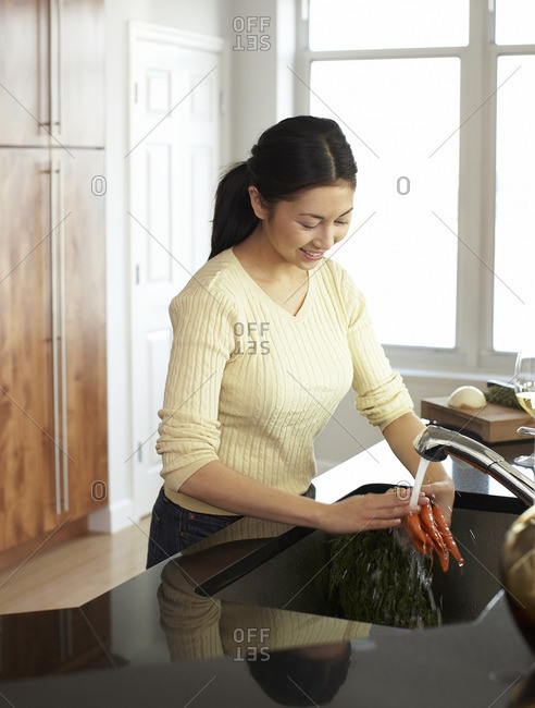 Woman washing carrots in kitchen