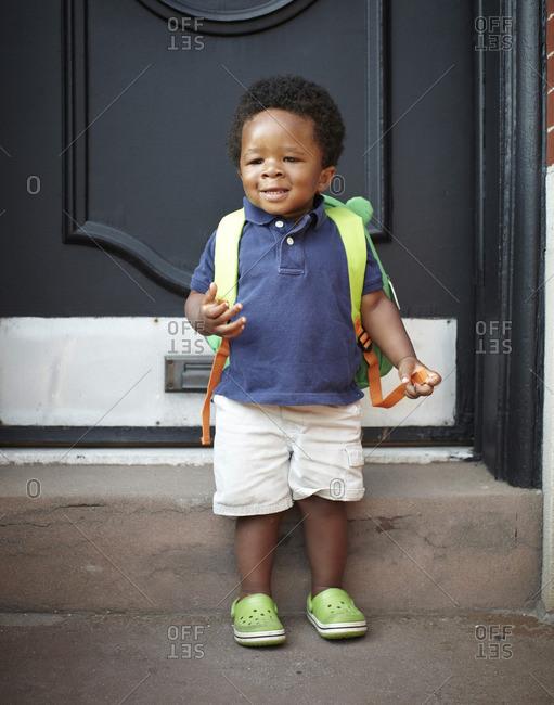African American baby wearing backpack
