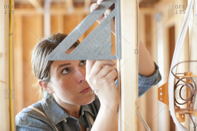 Caucasian carpenter measuring wall in unfinished room