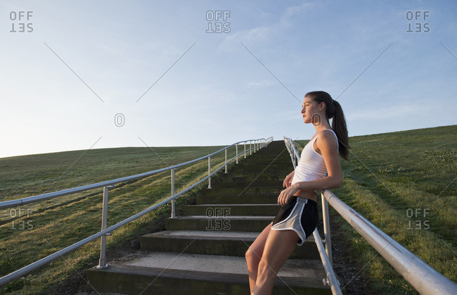 Caucasian runner leaning on staircase railing