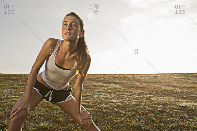 Caucasian runner stretching in field