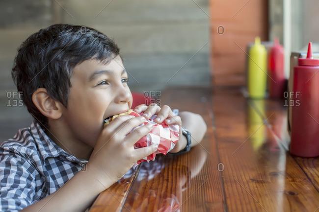 Mixed race boy eating burger in restaurant