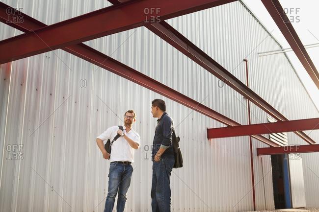 Men talking outside manufacturing plant