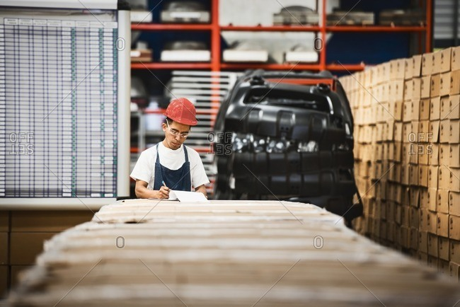Worker examining product in manufacturing plant