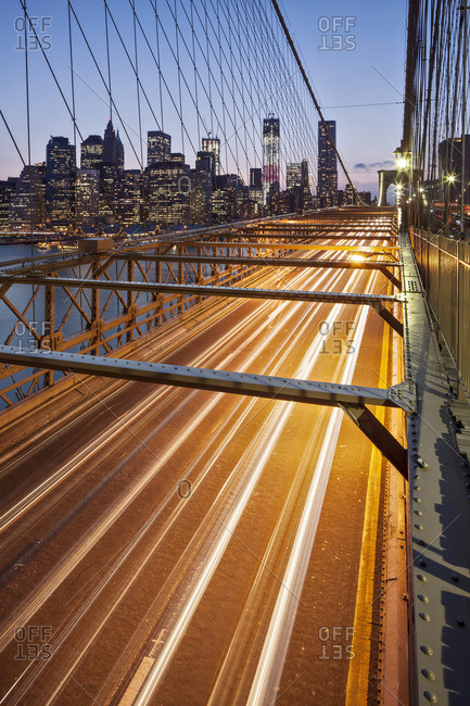 Traffic leaves colourful trails along the Brooklyn Bridge in New York, New York State, USA