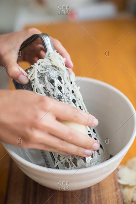 Hand shredding potatoes in close up