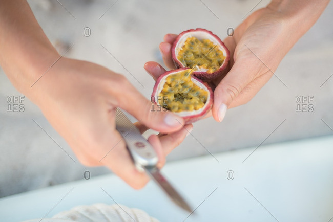 Hand opening up a passion fruit