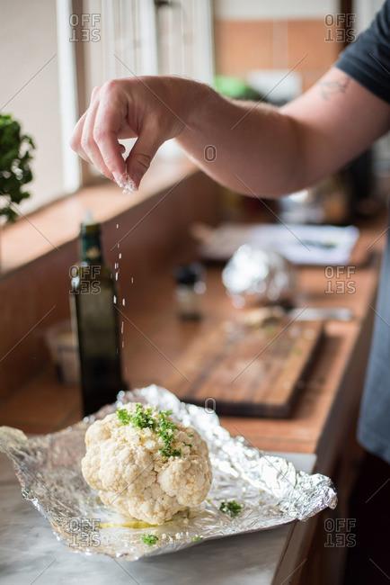 Hand seasoning herb stuffed cauliflower