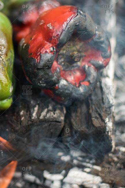 Peppers blackening on burning wood