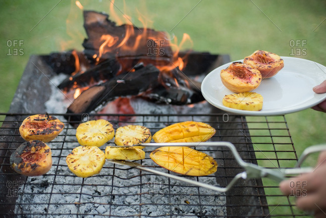 Person cooking fruit on a grill