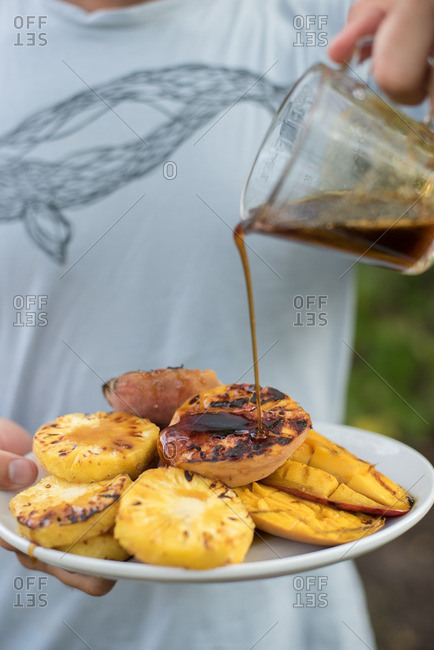 Person putting syrup on grilled fruit