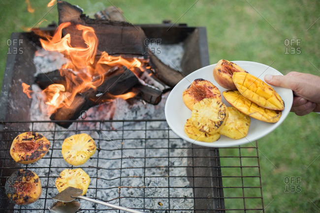Person roasting fruit on a grill
