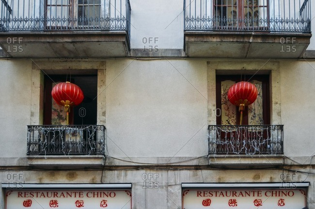 Detail of facade with balconies and red lamps