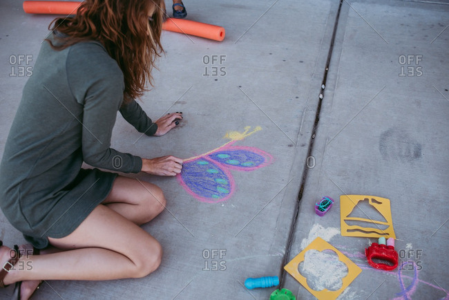 Woman drawing picture with colored chalk on the sidewalk