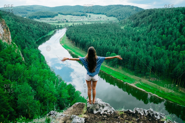 Girl standing on rocky ledge overlooking river with her arms spread
