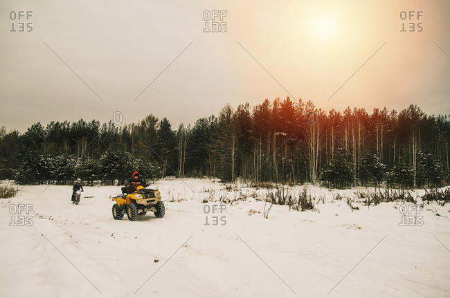 Caucasian men riding all-terrain vehicles in snowy forest