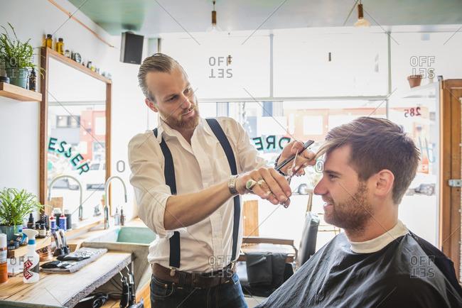 Caucasian stylist cutting hair of customer in barber shop