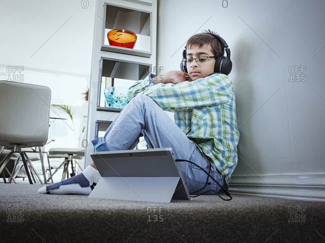 Mixed race boy using digital tablet on floor
