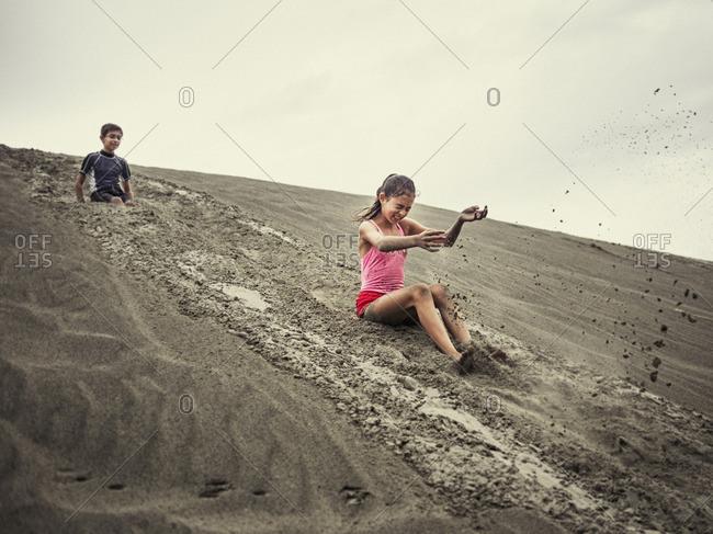 Children sliding on sand dune