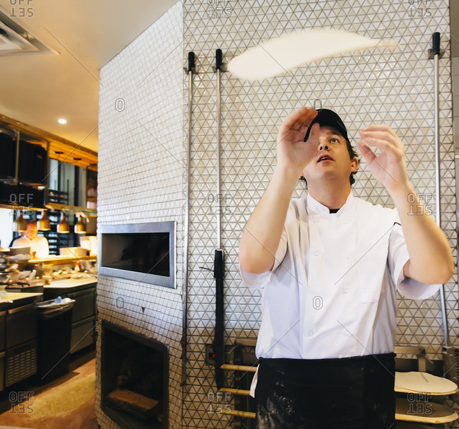 Chef tossing pizza dough in restaurant in kitchen