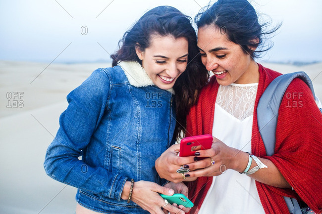 Mixed race women using cell phones
