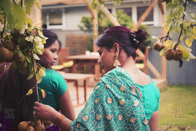 Women wearing Indian dresses in backyard
