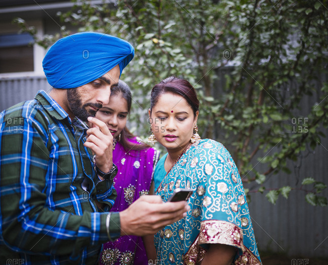 Family in traditional Indian clothing using cell phone