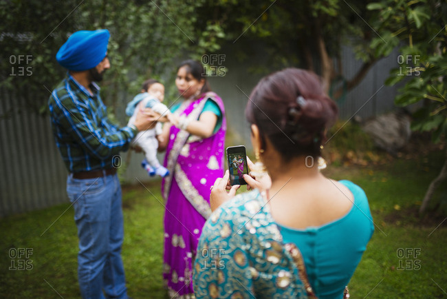 Woman photographing family with cell phone