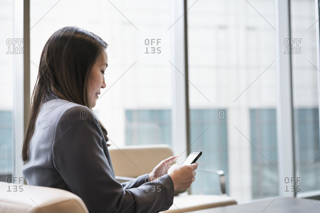 Japanese businesswoman using cell phone in office