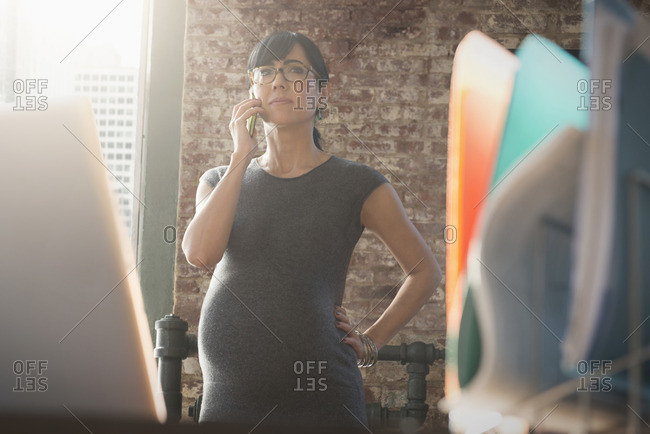 Pregnant Hispanic businesswoman talking on cell phone in office