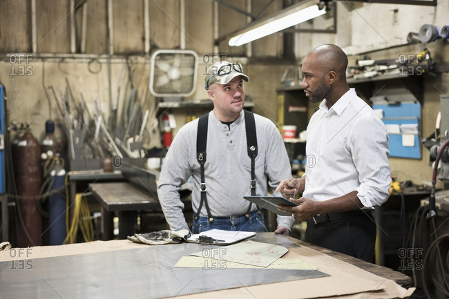 Worker and businessman using digital tablet in workshop