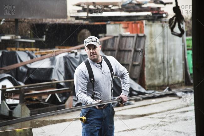 Caucasian worker carrying metal in workshop