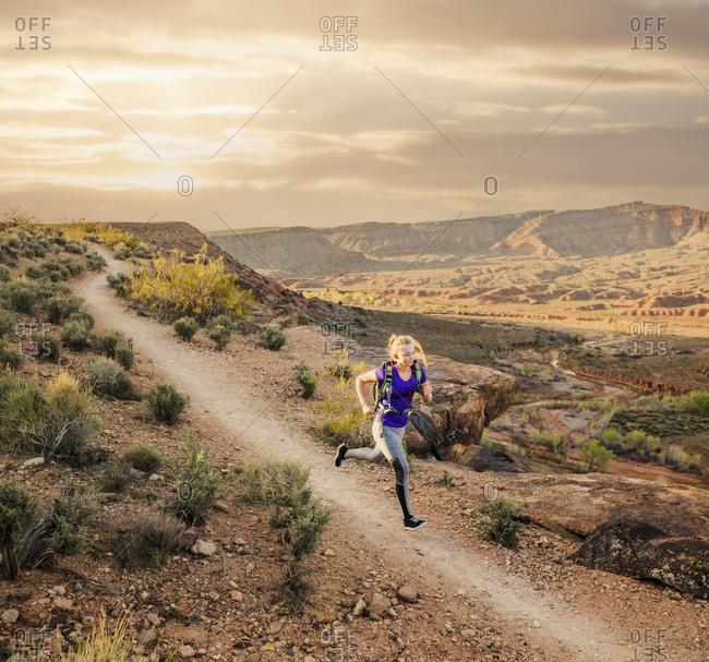 Caucasian woman running on remote dirt path
