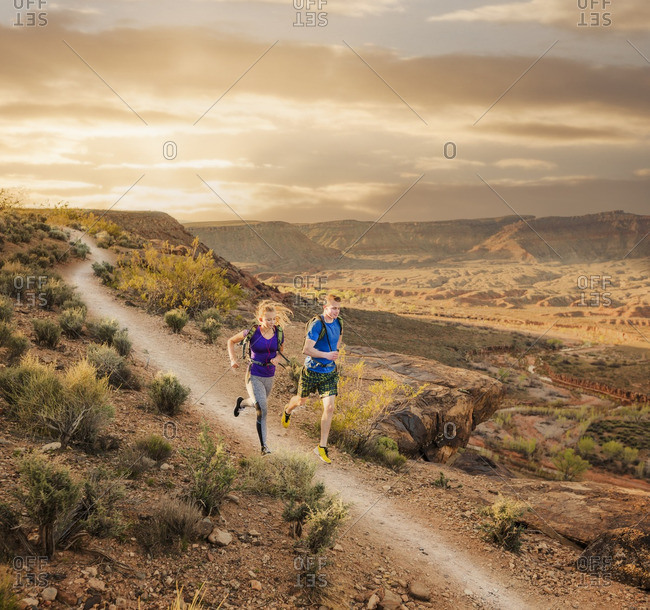 Caucasian couple running on remote dirt path
