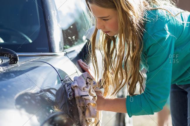 Caucasian girl washing car