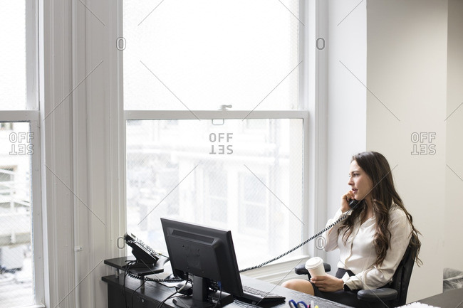 Caucasian businesswoman talking on telephone in office