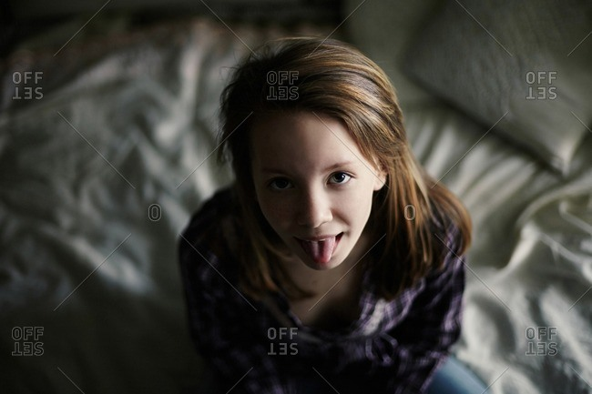 Caucasian teenage girl sticking out tongue