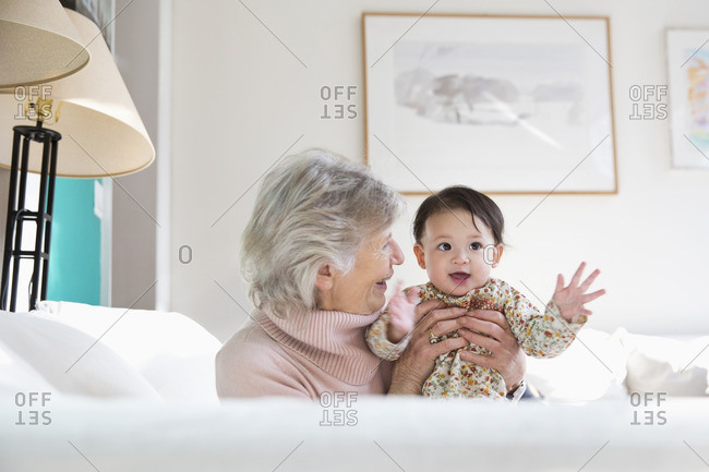 Grandmother and granddaughter hugging on sofa