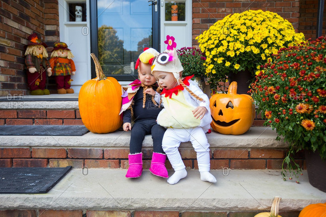A young Caucasian toddler boy and girl sitting on their decorated front porch dressed in Halloween costumes