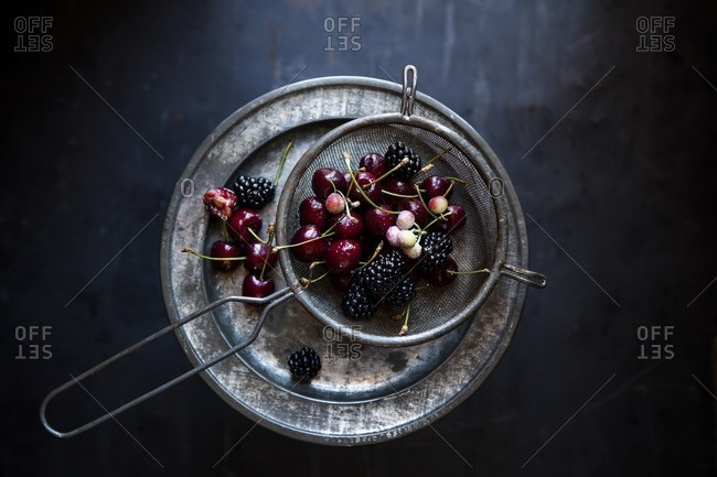 Fruits and berries served in a colander
