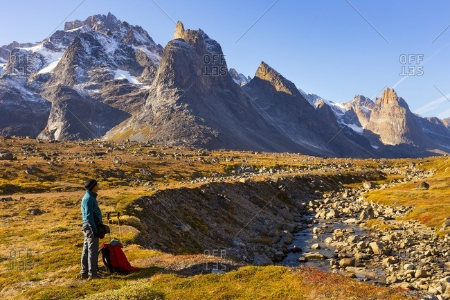 Man looking at mountains at sunset in Greenland