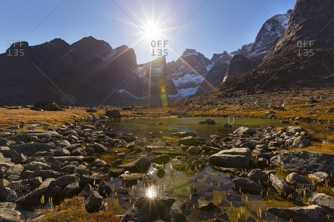 Sunburst over mountain and river in Greenland