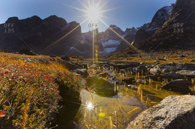 Sunburst with lens flare over mountain and river in Greenland
