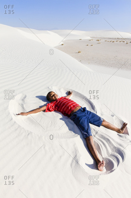 A young boy creating a 'sand angel' in the desert of the White Sands National Monument