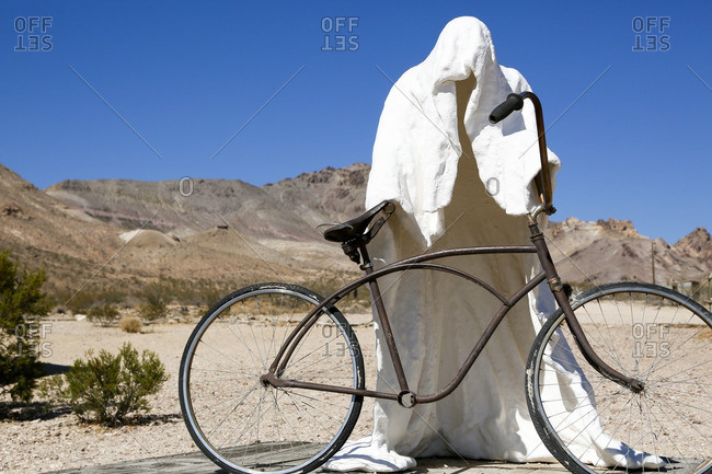 Rhyolite, Nevada - October 9, 2016: Ghost-like sculpture holding a vintage bicycle