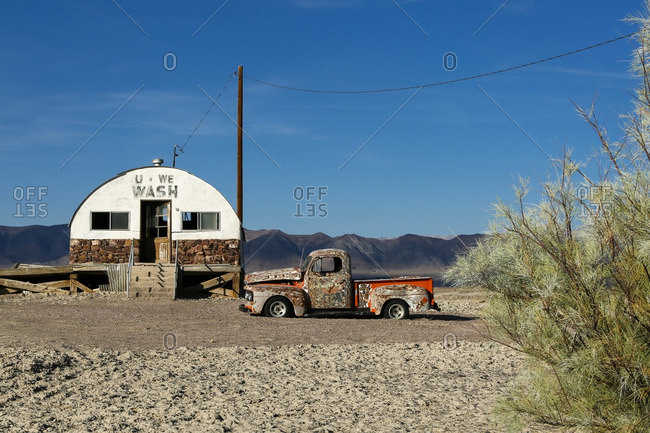 Tacopa, California - June 28, 2015: An abandoned camouflage painted truck in front of an old building in the desert