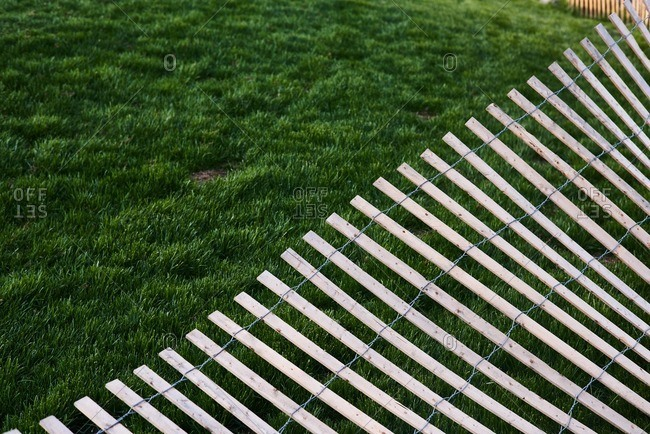 Abstract geometric shot of fallen wooden fence against green grass, divided diagonally