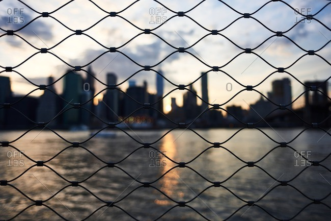 View from behind chain linked net to East River and blurred backlit silhouette of Manhattan skyline at dusk
